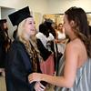 KEN YUSZKUS/Staff photo. Graduate Allie Kearney gets an embrace from a friend Corrine Johnson before the Beverly graduation.    6/07/15
