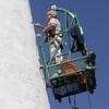 KEN YUSZKUS/Staff photo.   Joseph Nally repairs the stucco on the outside of Bakers Island Light Station.   6/30/15