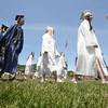 KEN YUSZKUS/Staff photo. Graduates proceed from the school toward the tent at the start of the Hamilton-Wenham graduation.    6/07/15