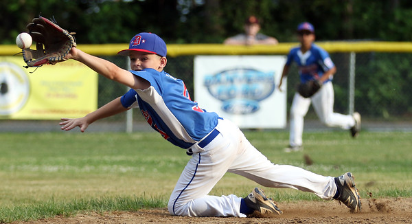DAVID LE/Staff photo. Danvers shortstop Payton Palladino makes an all out diving effort but can't manage to come up with a sharp hopper deep in the hole against Beverly on Wednesday evening. 6/29/16.