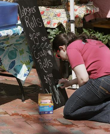 KEN YUSZKUS/Staff photo.    Erin Kudlik writes the specials on a chalkboard at the start of the Salem Farmers Market.      06/09/16