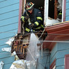 DAVID LE/Staff photo. Salem firefighters spray water down a hole in the gutter area in between the second and third floor of 38 Harbor Ave in Salem after a fire broke out on Friday afternoon. 6/24/16.
