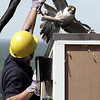 KEN YUSZKUS/Staff photo.   Massachusetts Division of Fisheries and Wildlife assistant director Thomas French fends off the diving mother peregrine falcon as he stands near the nest box that hold the three chicks. The bird's nest box is on top of 18-story Fox Hall at UMass Lowell.    06/08/16