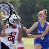 DAVID LE/Staff photo. Masco sophomore goalie Marissa Karras (28) tries to evade Danvers senior Allie Zunick, as she tries to clear the ball from her defensive zone on Thursday afternoon. 6/2/16.