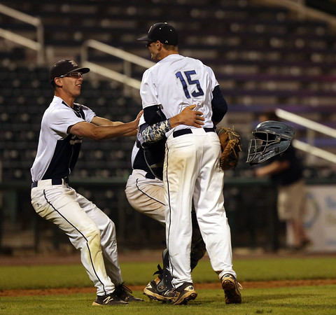DAVID LE/Staff photo. Danvers  junior Max Paul, left, and Matt Andreas, behind, sprint to greet senior captain Andrew Olszak (15) after he spun a complete game win over Reading to capture the D2 North Title at LeLacheur Park in Lowell on Sunday evening. 6/11/16.