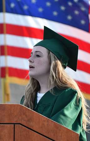 Framed by Old Glory herself, North Reading's Elizabeth Gravel a vetrinary sciences graduate, performs the National Anthem for the graduation ceremony.<br /> <br /> Photo by joebrownphotos.com