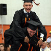 DAVID LE/Staff photo. Beverly High School graduate Colin Oliver jumps on the shoulders of his twin brother Casey, as they piggyback their way back to their seats after receiving their diplomas on Sunday afternoon. 6/5/16.