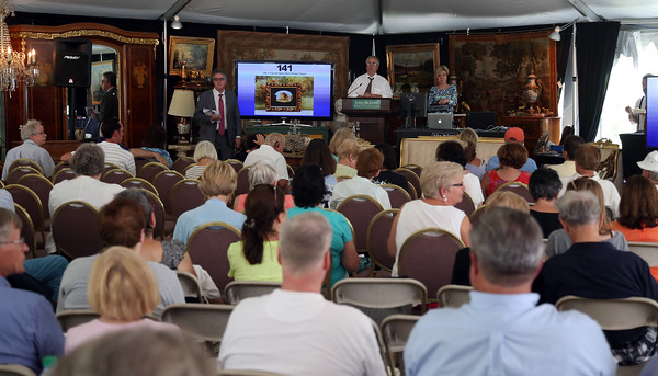 DAVID LE/Staff photo. People crowded under a tent on the grounds of the Henry Audesse estate on Larch Row in Wenham for an auction of many of the valuables that were inside the mansion. The property was also auctioned off, with a high price of 1.5$ million dollars as the final bid for the live auction, but was not approved as a selling price by a trustee. 7/1/16.