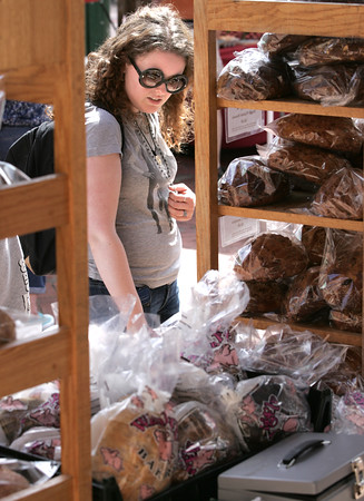 KEN YUSZKUS/Staff photo.    Amber Shannon looks over various breads on sale at the Salem Farmers Market.      06/09/16