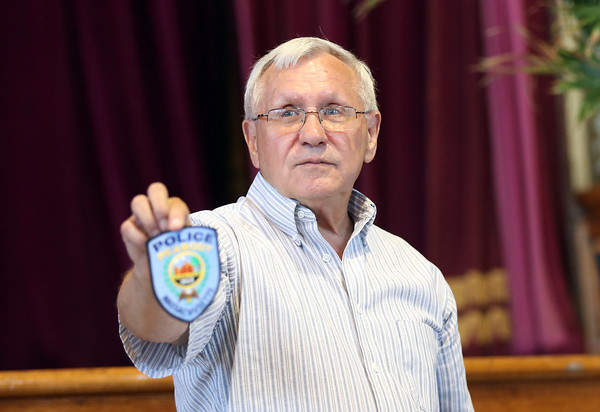 DAVID LE/Staff photo. Former Peabody Mayor Michael Bonfanti holds up an old police patch that was packed inside a time capsule buried in the Peabody monument.  6/29/16.
