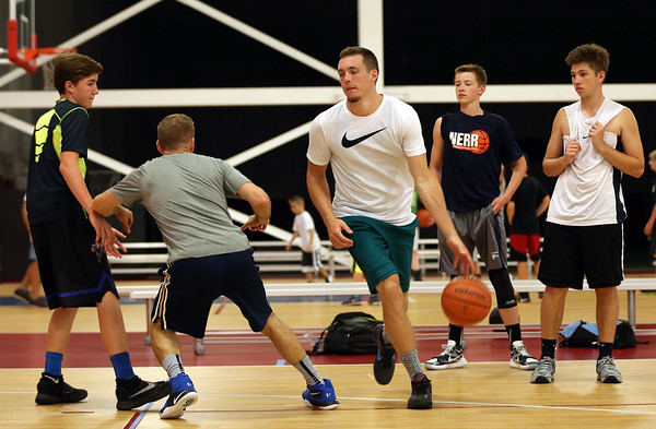 """DAVID LE/Staff photo. Portland Trailblazers guard and former St. John's Prep and Notre Dame standout, Pat Connaughton runs through a pick and roll drill with coach Mike Crotty, center, as campers look on during the Pat Connaughton """"With Us"""" Camp on Tuesday afternoon. 6/28/16."""