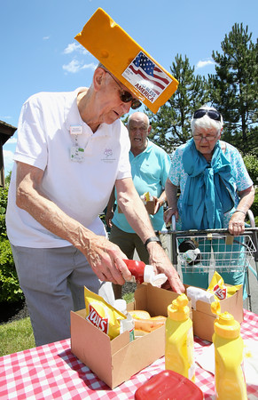 KEN YUSZKUS/Staff photo.  Resident Don Bade applies ketchup to a hotdog. A lunch of hotdogs, potato chips, and water were given out after the 4th of July parade at Brooksby Village in Peabody.  06/30/16