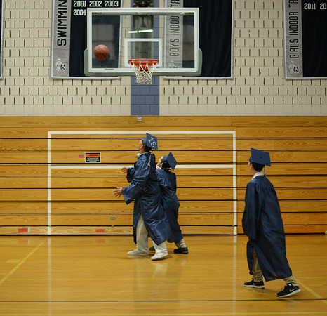 PAUL BILODEAU/Staff photo.  A group of students pay basketball while they wait to head to their ceremony during Hamilton-Wenham Regional High School's graduation ceremony in a tent on the football field at the school.
