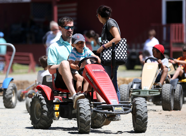 DAVID LE/Staff photo. Dylan Nazarian, 3, of Reading, sits on his father Cory's lap, while driving a go-kart at the annual Strawberry Festival held at Connors Farm in Danvers as part of the Danvers Family Festival. 6/18/16.