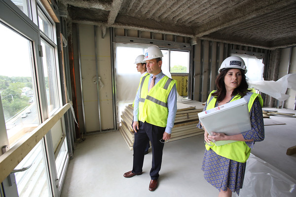KEN YUSZKUS/Staff photo.   From left,  leasing associate Aaron Smith, vice president/general manager Stephen Drohosky, and vice president of marketing & sales Liz Speranzella admire the view while walking through the Cummings Center's new condo complex under construction, Elliott Landing.       06/09/16