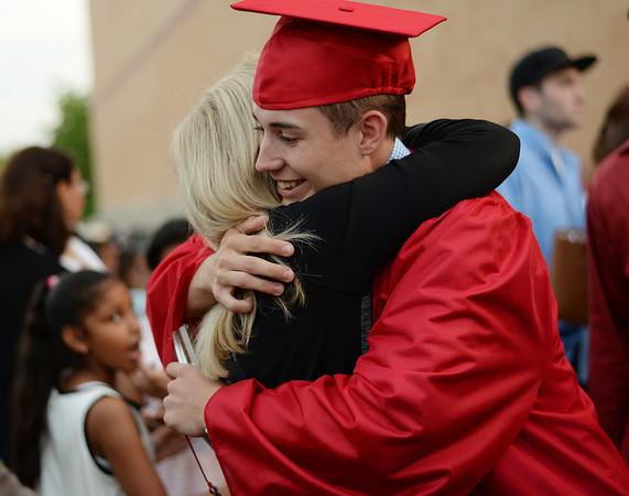 PAUL BILODEAU/Staff photo. Joanne Pinkham hugs her grandson, Devin Pinkham, at the end of Salem High School's graduation ceremony in the high school's field house.