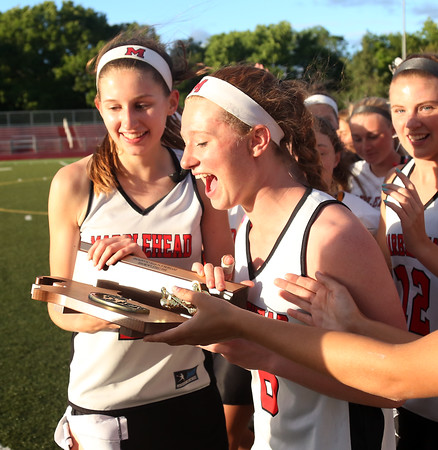 DAVID LE/Staff photo. Marblehead senior captains Kylie Cronin, right, and Corinne Mayle, left, happily carry the D2 North trophy off the field, following the Magicians 18-8 win over Ipswich on Thursday evening. 6/9/16.