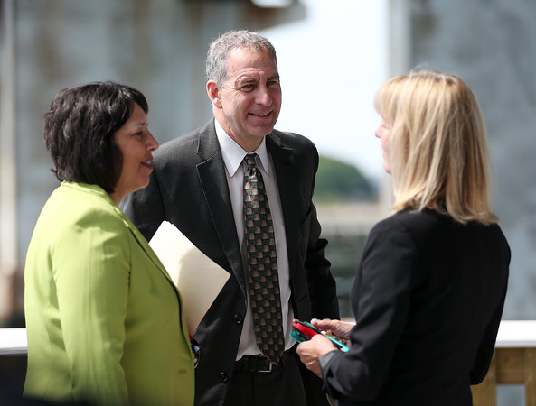 DAVID LE/Staff photo. State Representative Jerry Parisella, center, chats with Salem Mayor Kim Driscoll, left, and State Senator Joan Lovely, following a ribbon cutting ceremony at the new Harborwalk at the base of the Beverly-Salem Bridge. 6/20/16.