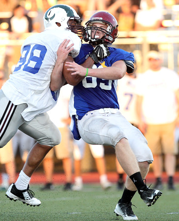 DAVID LE/Staff photo. Gloucester defensive lineman John Philpott tries to get through the grip of Lynn English lineman Jeremy Garcia while rushing the quarterback. 6/30/16.