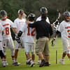 Beverly: During the North Division 2 playoff quarterfinal held at Endicott College on Saturday afternoon. Beverly beat Burlington 14-9. Beverly's Hunter Spencer (12) scored three goals during the game. He is being congratulated by assistant coach Jim LaSelva, right at the end of the game. Photo by Allegra Boverman