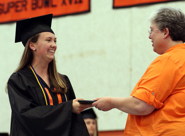 DAVID LE/Staff photo. Beverly High School Emma Leighton smiles while receiving her diploma from Kris Silverstein, President of the School Committee on Sunday afternoon. 6/5/16.