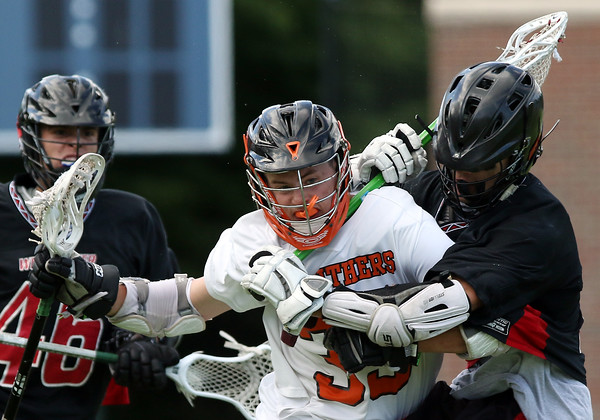 DAVID LE/Staff photo. Beverly junior midfielder Kevin Flaherty (33) bowls through a stick check to the neck thrown by Winchester junior Walker Huff, right. 6/10/16.
