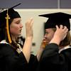 PAUL BILODEAU/Staff photo. Izabella Lidrbauch helps friend Olivia Kubaska with her mortarboard before the start of  Ipswich High School's graduation ceremony in the field house at the school.