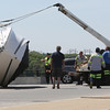 KEN YUSZKUS/Staff photo.     A boat is righted after ending up on it's side in the street. It fell off a trailer while being transported on Bridge Street at the end of the bridge in Salem.     06/01/16