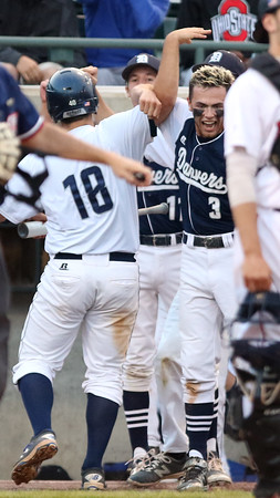 DAVID LE/Staff photo. Danvers sophomore Zach Dillon (18) gets greeted by senior captain Tim Unczur (3) after he scored one of the Falcons seven 4th inning runs. 6/11/16.