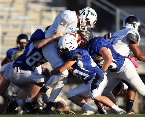 DAVID LE/Staff photo. North defenders Ryan Garrity, left, of Beverly, and Frank Falco, of Peabody, wrap up South quarterback and Pingree quarterback Griffin Beal for a loss of yards. 6/30/16.