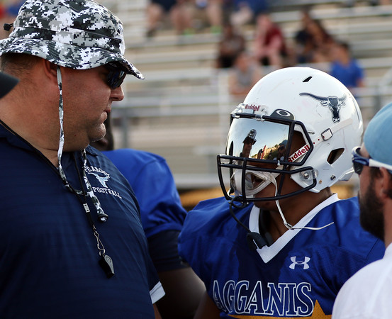 DAVID LE/Staff photo. Peabody head coach Mark Bettencourt talks with his star running back Dougie Santos on the sidelines of the Agganis football game on Thursday evening. 6/30/16.