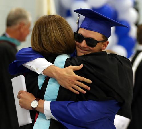 DAVID LE/Staff photo. Danvers graduate Danny Lynch hugs principal Susan Ambrozavitch after receiving his diploma. 6/11/16.
