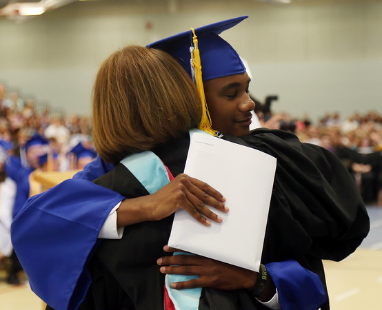 DAVID LE/Staff photo. Danvers senior Tre Crittendon gives a heartfelt hug to Danvers High Principal Susan Ambrozavich, after receiving his diploma on Saturday afternoon. 6/11/16.