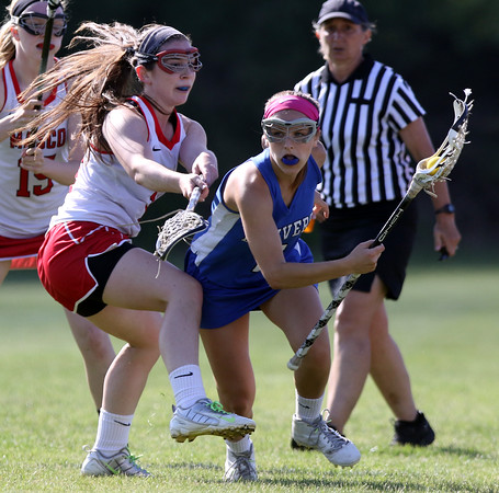 DAVID LE/Staff photo. Danvers senior Anne Tarricone tries to spin past Masco senior captain Dayna Eidle, left, and turn upfield on Thursday afternoon. 6/2/16.