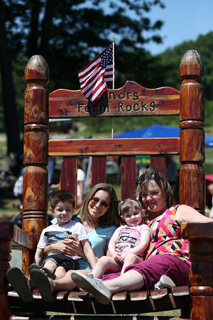 DAVID LE/Staff photo. Cameron, 4, and Madelyn Sweeney, left, and Lila, 3, and Heather Shattuck, of Georgetown, pose for a photograph on top of a giant wooden chair at the annual Strawberry Festival held at Connors Farm in Danvers as part of the Danvers Family Festival. 6/18/16.