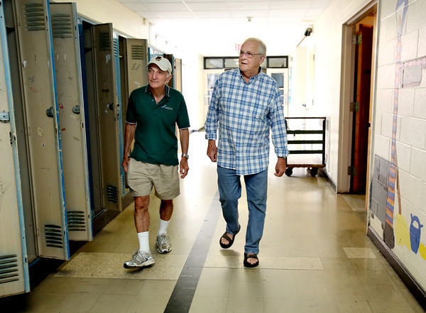 """KEN YUSZKUS/Staff photo.    Jim Terlizzi, left, and Bob Simons walk the hallways of the Higgins Middle School. They were both science teachers in the school when it was the high school during the late sixties. Like others, the public got to say """"goodbye"""" to the old middle school on Monday.    06/27/16"""