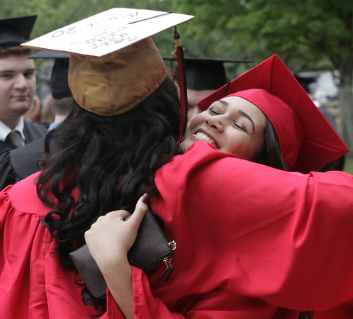 KEN YUSZKUS/Staff photo.   Marblehead High School graduates Gabriela Gonzalez and Janely Rodriguez greet and hug outside the school before the ceremony.     06/12/16