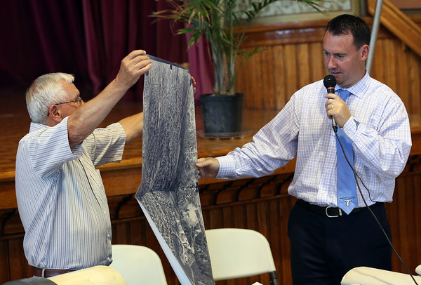 DAVID LE/Staff photo. Former Peabody Mayor Michael Bonfanti, left, helps current Peabody Mayor Ted Bettencourt, open items in a time capsule from 1989 inside Peabody City Hall on Wednesday afternoon. Bonfanti holds up an old map as Bettencourt tries to identify notable landmarks. 6/29/16.