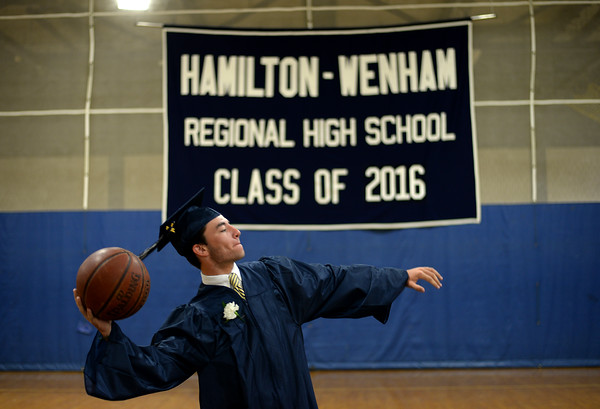 PAUL BILODEAU/Staff photo. Colin Hubbard plays a little basketball while students wait to head to their graduation ceremony during Hamilton-Wenham Regional High School's graduation ceremony in a tent on the football field at the school.