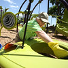 KEN YUSZKUS/Staff photo.     Volunteer Jaye Cuffe cleans the new playground equipment at the Dane Street playground. A ribbon cutting is scheduled for the opening on Sunday.    06/06/16