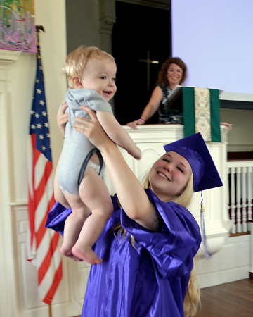 RYAN HUTTON/ Staff photo<br /> Northshore Recovery High School graduate Haley Conley hoists her 11-month-old son Joel into the air after giving her graduation speech at the school's commencement ceremony at the Second Congregational Church in Beverly on Wednesday night.