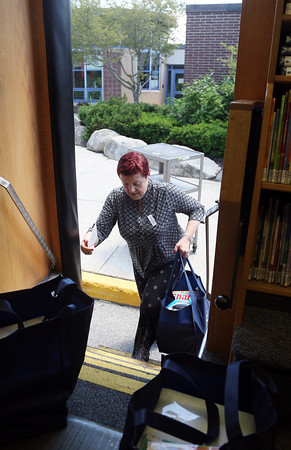 DAVID LE/Staff photo. Longtime Beverly Bookmobile Librarian Linda Carvaggio is retiring from driving the Bookmobile after over twenty years. Carvaggio hauls a couple heavy bags of books up the steps of the Bookmobile outside the Hannah School on Brimbal Ave. 6/21/16.