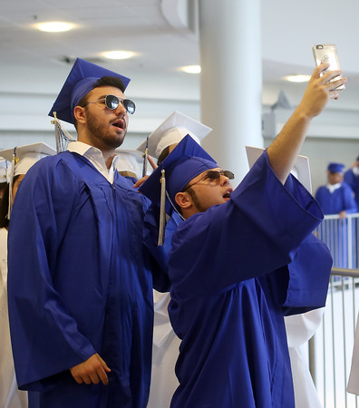 DAVID LE/Staff photo. Two Swampscott High School graduates take a SnapChat before entering graduation on Sunday afternoon. 6/5/16.