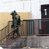 KEN YUSZKUS/Staff photo.    A suited up state police bomb technician exits the back door of Bertucci's Italian Restaurant where a reported suspicious device was found in the restaurant.     06/13/16