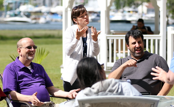 DAVID LE/Staff photo. Ronald Bergenheim, Lauren Quirion, and Matthew Castiglione, sign while chatting away at a BBQ celebration held at the New England Homes for the Deaf in Danvers to commemorate their 115th year. 6/9/16.