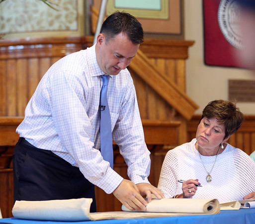 DAVID LE/Staff photo. Peabody Mayor Ted Bettencourt unrolls a scroll of old maps and floor plans in a time capsule from 1981. 6/29/16.