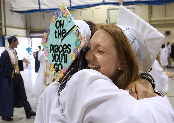 KEN YUSZKUS/Staff photo.    Peabody Veterans Memorial High School graduates Marina DeMild, left, and Lizzie Godschall hug each other before the start of their graduation.       06/03/16