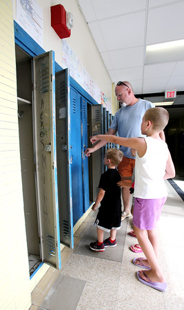 "KEN YUSZKUS/Staff photo.    Scott Mangino and his children Haylee, 7, Madison, 6, and Bentley, 4, examine the lockers in the hallways of the Higgins Middle School. Scott went to the school in 1984-85. Like others, the public got to say ""goodbye"" to the old middle school on Monday.    06/27/16"
