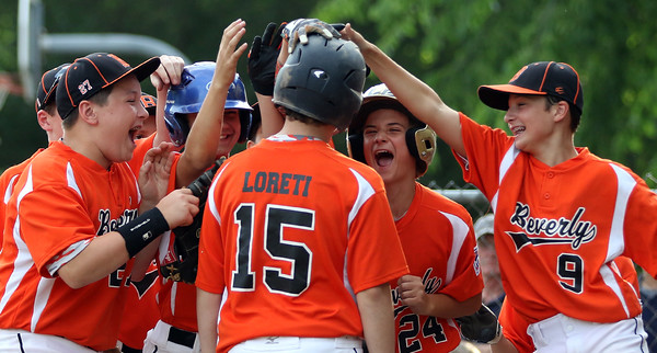 DAVID LE/Staff photo. Beverly players mob teammate Joey Loreti after he launched a 3-run home run to dead center field against Danvers. 6/29/16.