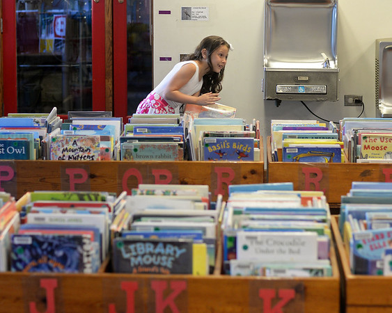 RYAN HUTTON/ Staff photo<br /> Claire Buckley, 7, searches the shelves of the Salem Public Library's children's section during the library's kickoff event for it's kid's summer reading program on Wednesday.